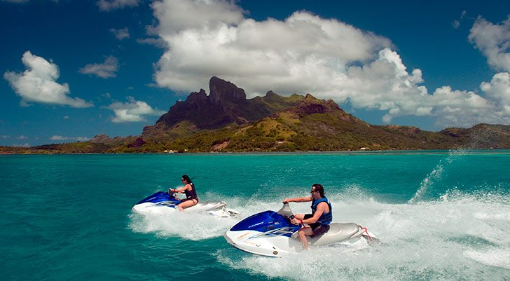 Two jet ski riders in front of a tropical rocky island
