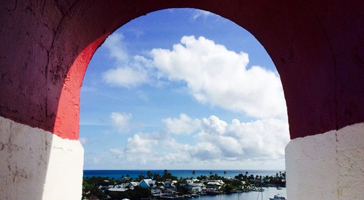 Red archway shows view of white clouds over the Caribbean Sea in Abaco Islands, Bahamas