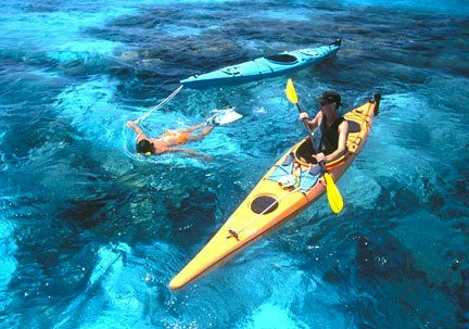 Couple kayaking and snorkeling in clear blue water of Belize