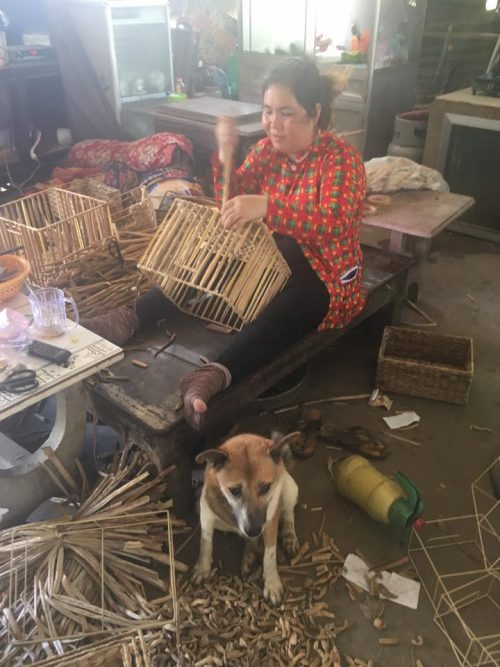 Basketweaver in workshop with her dog AQUA MEKONG