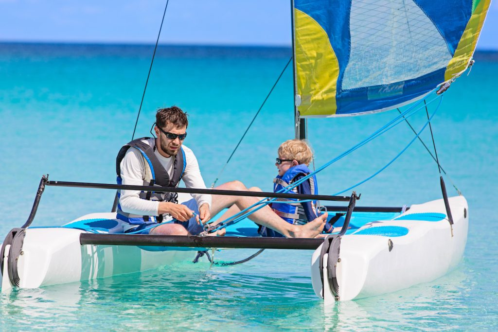 father and son, enjoying sailing together at hobie cat catamaran