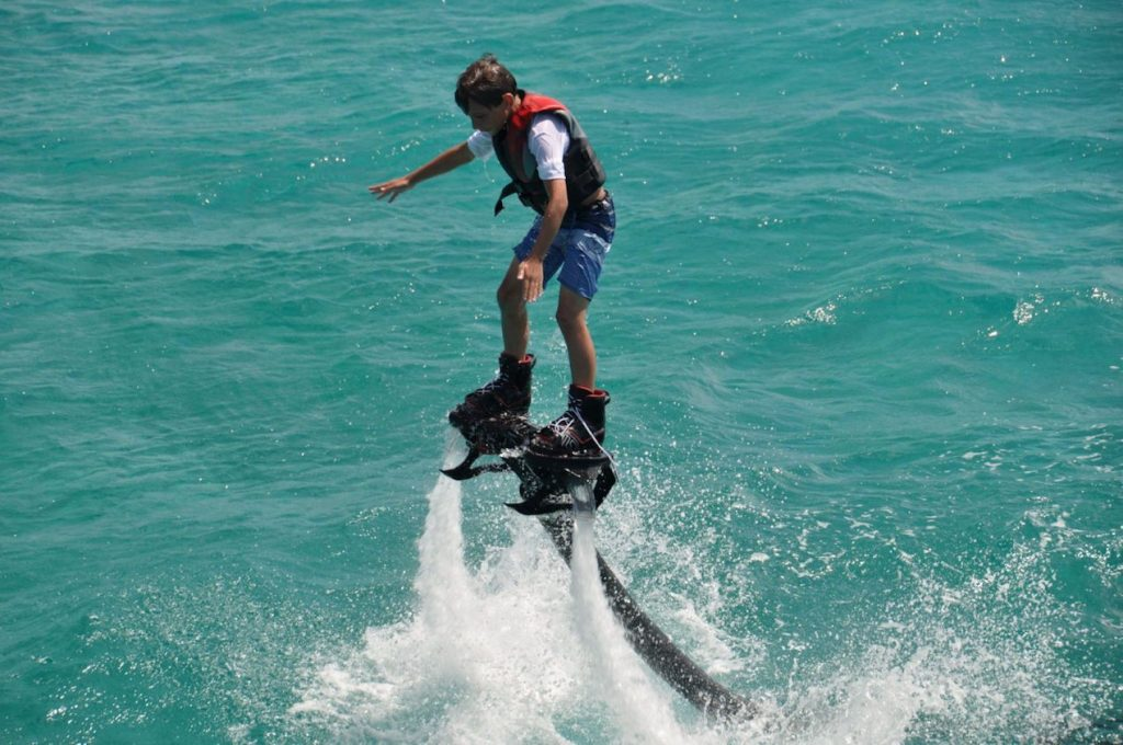 Teen rider on fly board off motor yacht