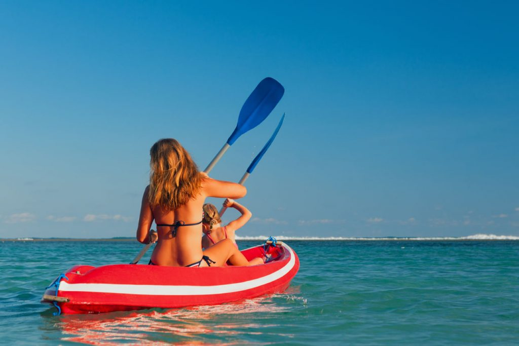 Mother and daughter paddling in a kayak in The Caribbean