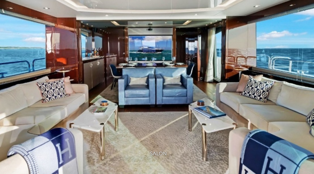 Salon with blue chairs and TV on the 86ft motor yacht Enterprise