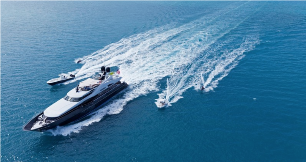123ft motor yacht TEMPTATION traveling fast on the water, flanked by toys and tenders
