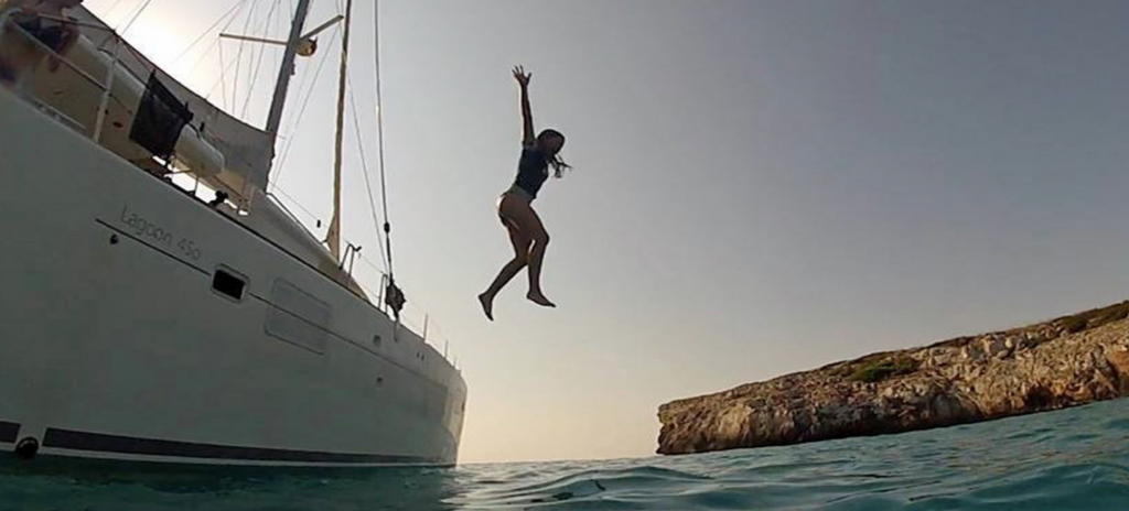 Girl jumping from the sailing yacht HAWKEYE into the Mediterranean