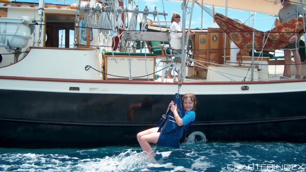 Girl on a Swing off the 72ft sailing yacht BONNIE LYNN, a modified version of designer Merrit Walter's Trade Rover Schooner