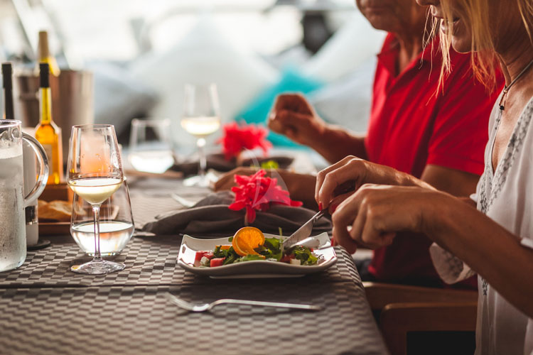 Passenger dining on salad with orange on the 62ft sailing yacht catamaran OCEAN VIEW