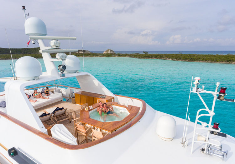 Couple lounging in the Jacuzzi and family on the sundeck aboard the motor yacht LADY J