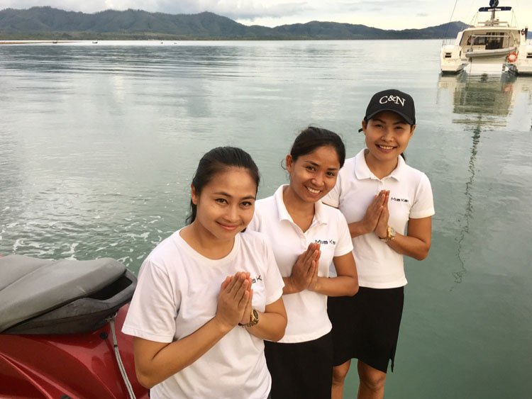 Three Thai women and namaste wishers by a boat on the water welcome guests to Thailand