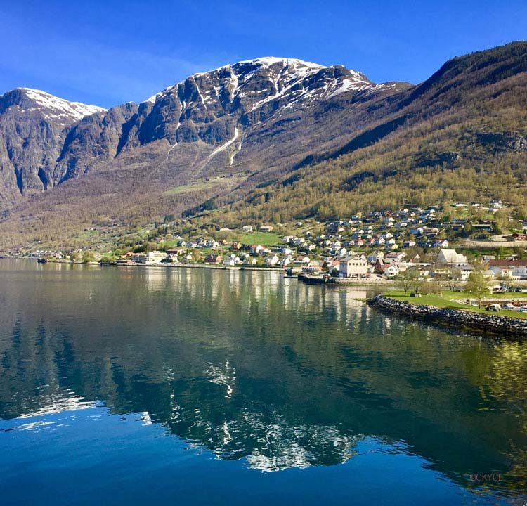 Town and snow-topped mountain reflected in water Norway