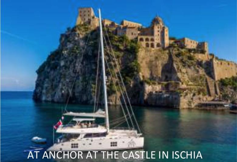 70ft sailing catamaran OMBRE BLU 3 at anchor at castle on Ischia, Amalfi Coast, Italy