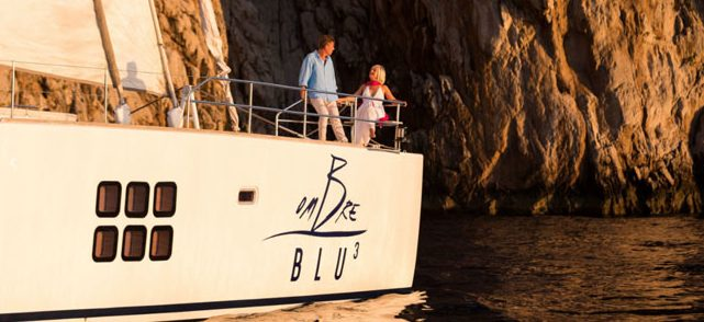 Couple enjoying Italian sun and Amalfi Coast cliffs on deck of 70ft luxury Sunreef catamaran S-Y Ombre Blu 3