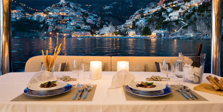 Dining Table for evening dinner on the 70ft Sunreef sailing yacht catamaran Ombre Blu 3 moored off Positano, Italy on the Amalfi Coast