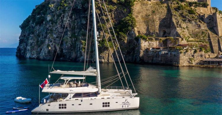 70ft Sunreef sailing catamaran OMBRE BLU³ off an Amalfi Coast Italy fort in the Western Mediterranean