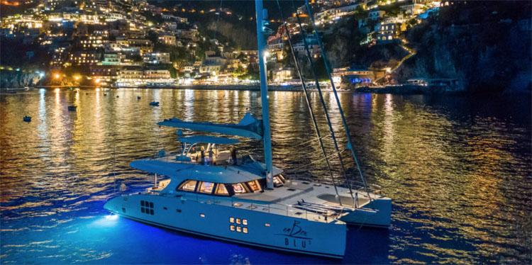 70ft Sunreef sailing catamaran OMBRE BLU moored off Positano on the Amalfi Coast in Italy at night