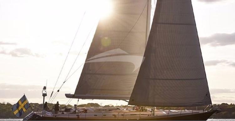 Sunshine kissing sail of 82ft Swan sailing yacht AQUILA at sea