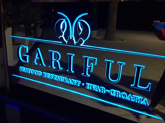 Gariful restaurant table and chairs on glass floor above fish tank