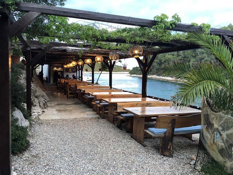 Restaurant with tables and trellis along the water in Croatia