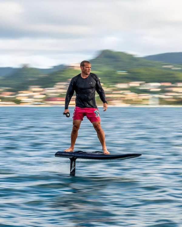 Colin Guinn riding an electric hydro foil board above the water of sailing catamaran TWIN FLAME