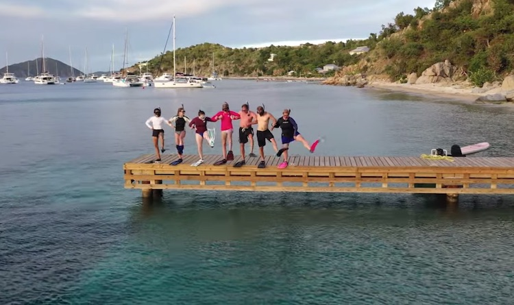 Group of snorkelers from the sailing catamaran LOLALITA dancing on a dock in snorkel gear.