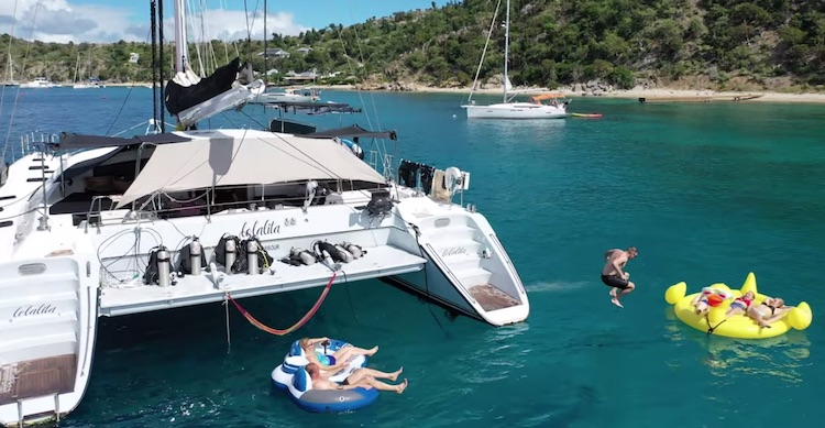Guest cannonballing giant rubber duck float off sailing catamaran LOLALITA in the British Virgin Islands