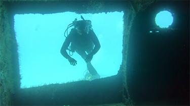 SCUBA diver swimming through hole in underwater shipwreck off sail catamaran LOLALITA in the British Virgin Islands