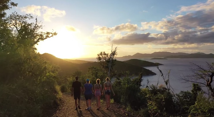 Four family member guests on the sail catamaran LOLALITA take a sunset walk on a hill path in the British Virgin Islands