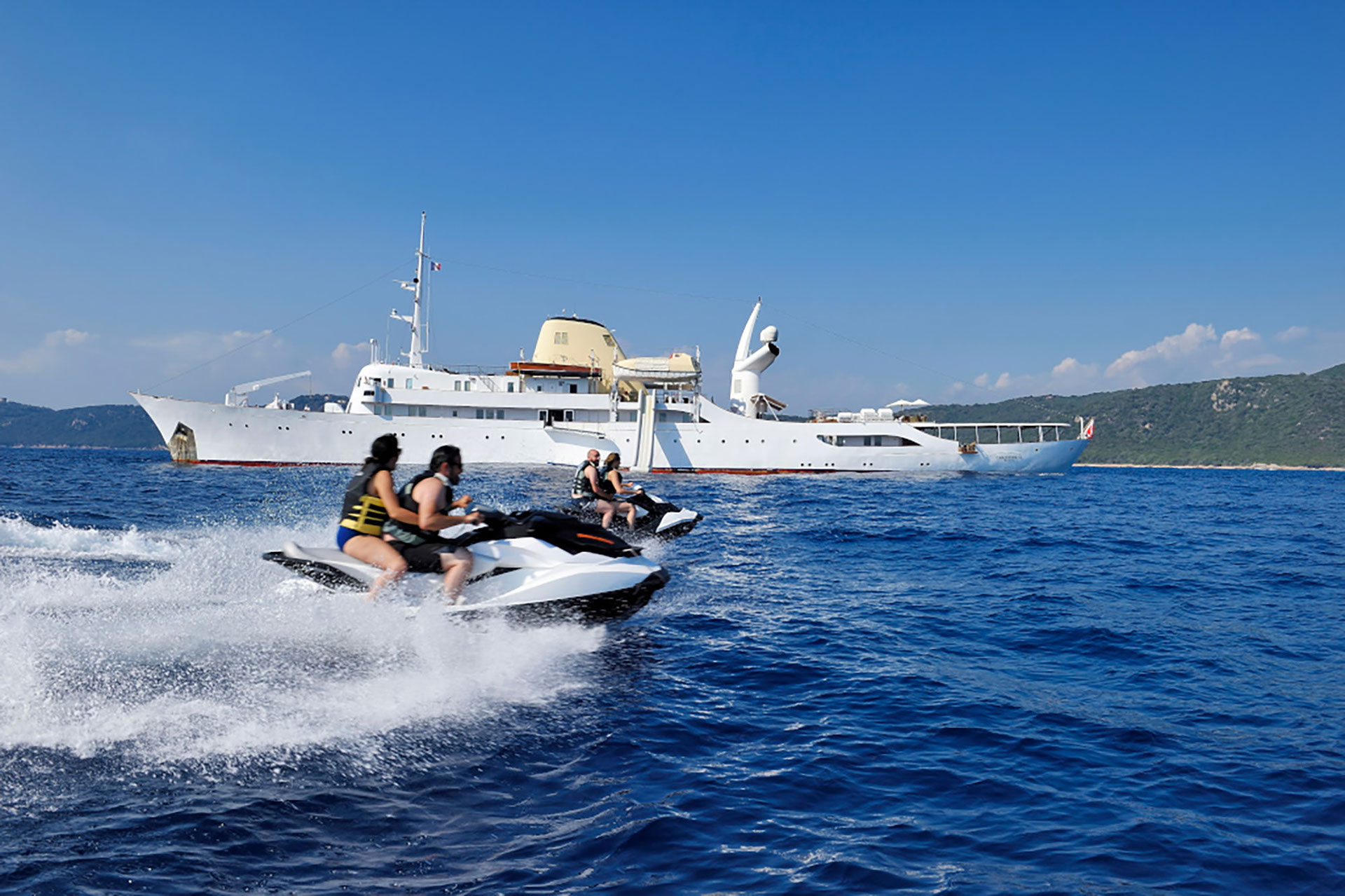 Couples zooming by 325ft superyacht CHRISITINA O on her jet skis
