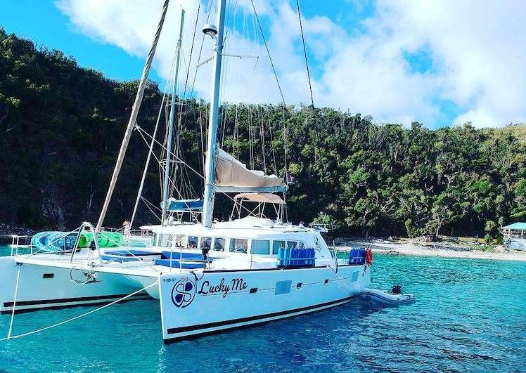 Rear view of 51ft Lagoon sailing catamaran LUCKY ME moored off tropical beach